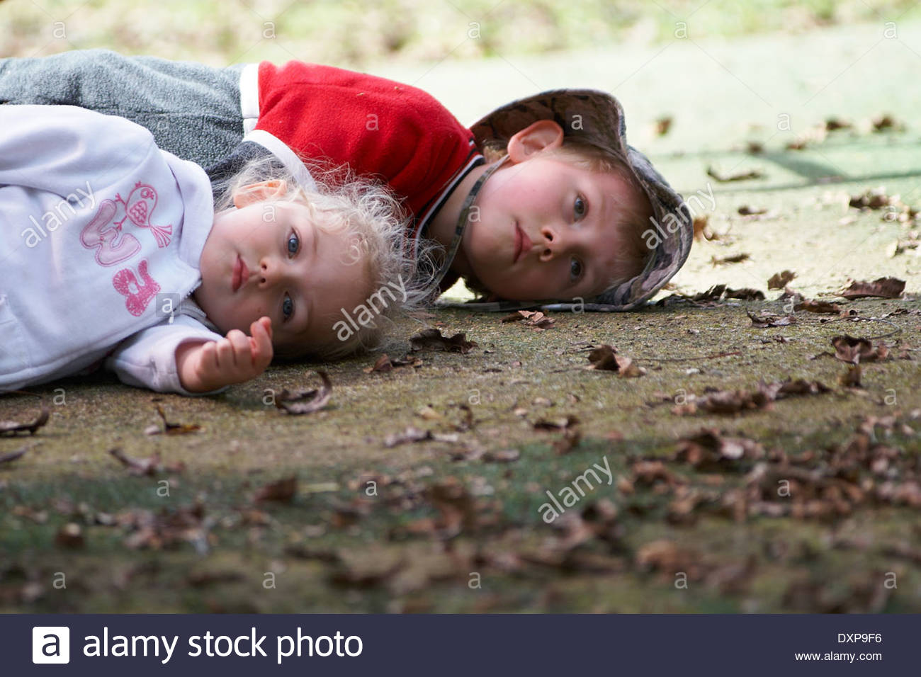 Brother and sister, lying on fake grass at school - doll-like / lifeless / 'playing dead' - a concerning, dramatic response to the camera's intrusion. - Stock Image