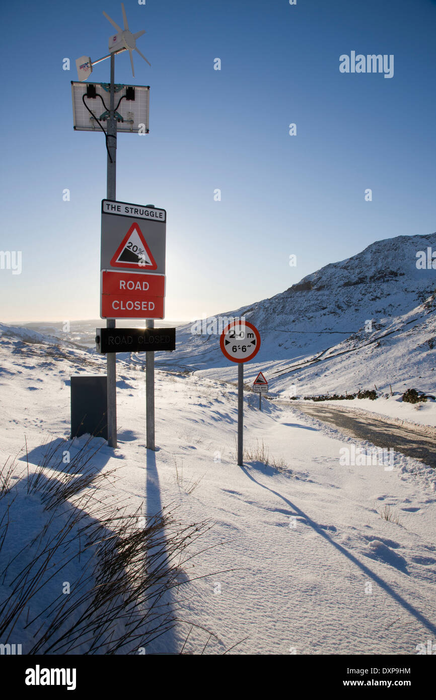Wind and solar powered road sign showing closure of mountain highway kirkstone pass the lake district england - Stock Image