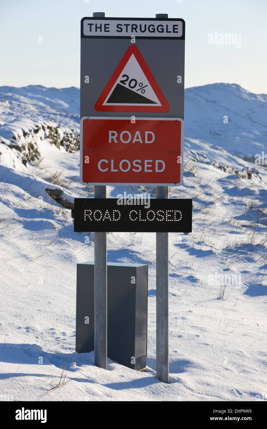 Road sign showing closure of the kirkstone pass mountain highway mid winter in the lake district england - Stock Image