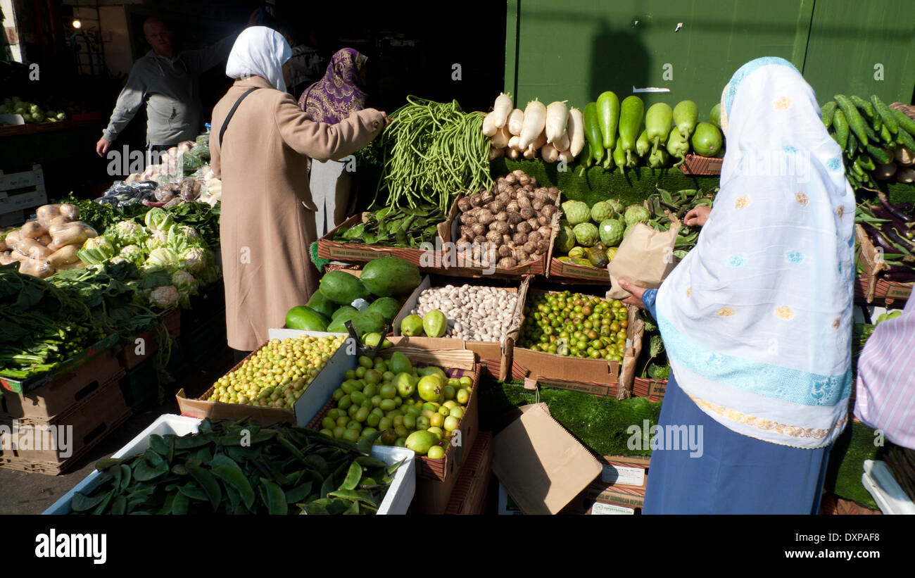 Muslim women food shopping buying fruit and vegetables at a stall shop in Whitechapel High Street Market East London, England UK KATHY DEWITT - Stock Image