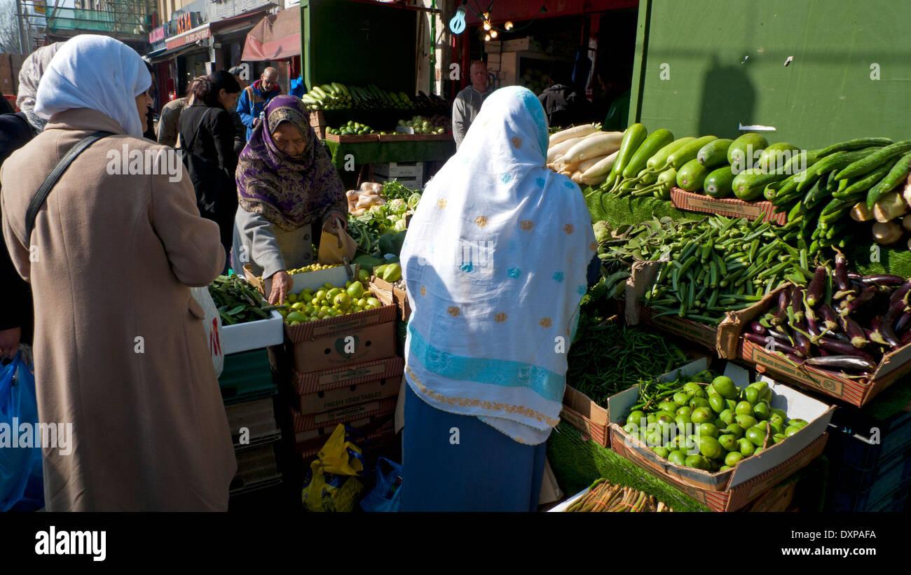 Muslim women buying vegetables in Whitechapel Road Market East London, UK KATHY DEWITT - Stock Image