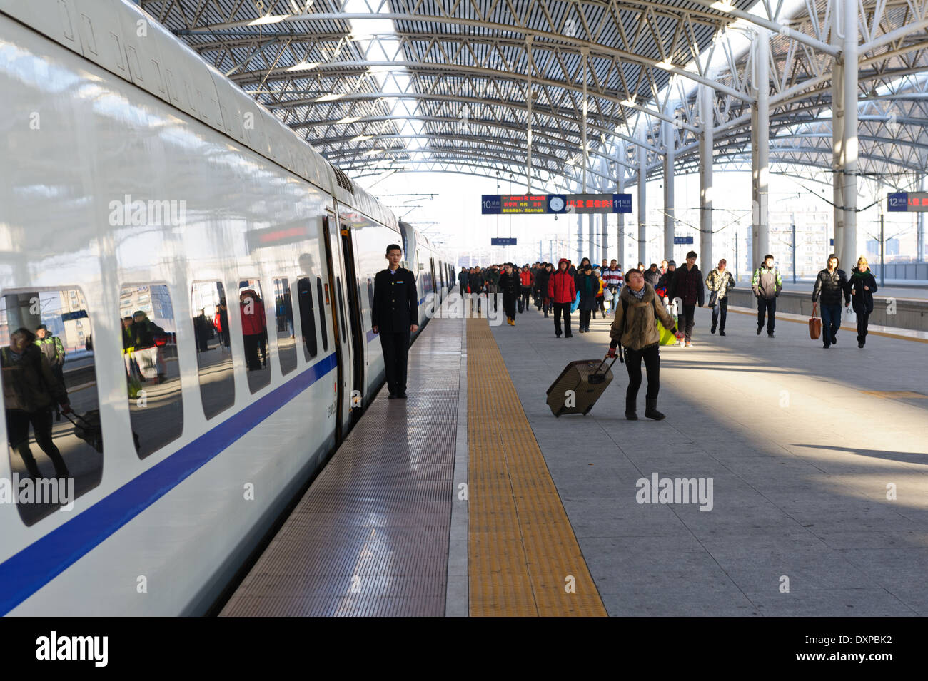 Crew member standing to attention while passengers disembark high speed train.  Jilin train station. Jilin Province, China - Stock Image