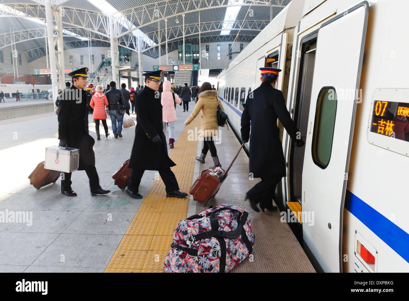 Crew entering high speed train at Jilin train station . Jilin Province, China - Stock Image