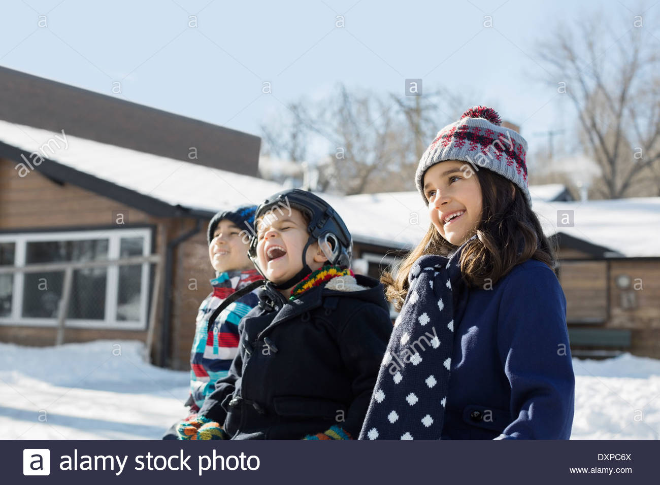 Portrait of siblings sitting on bench outdoors - Stock Image
