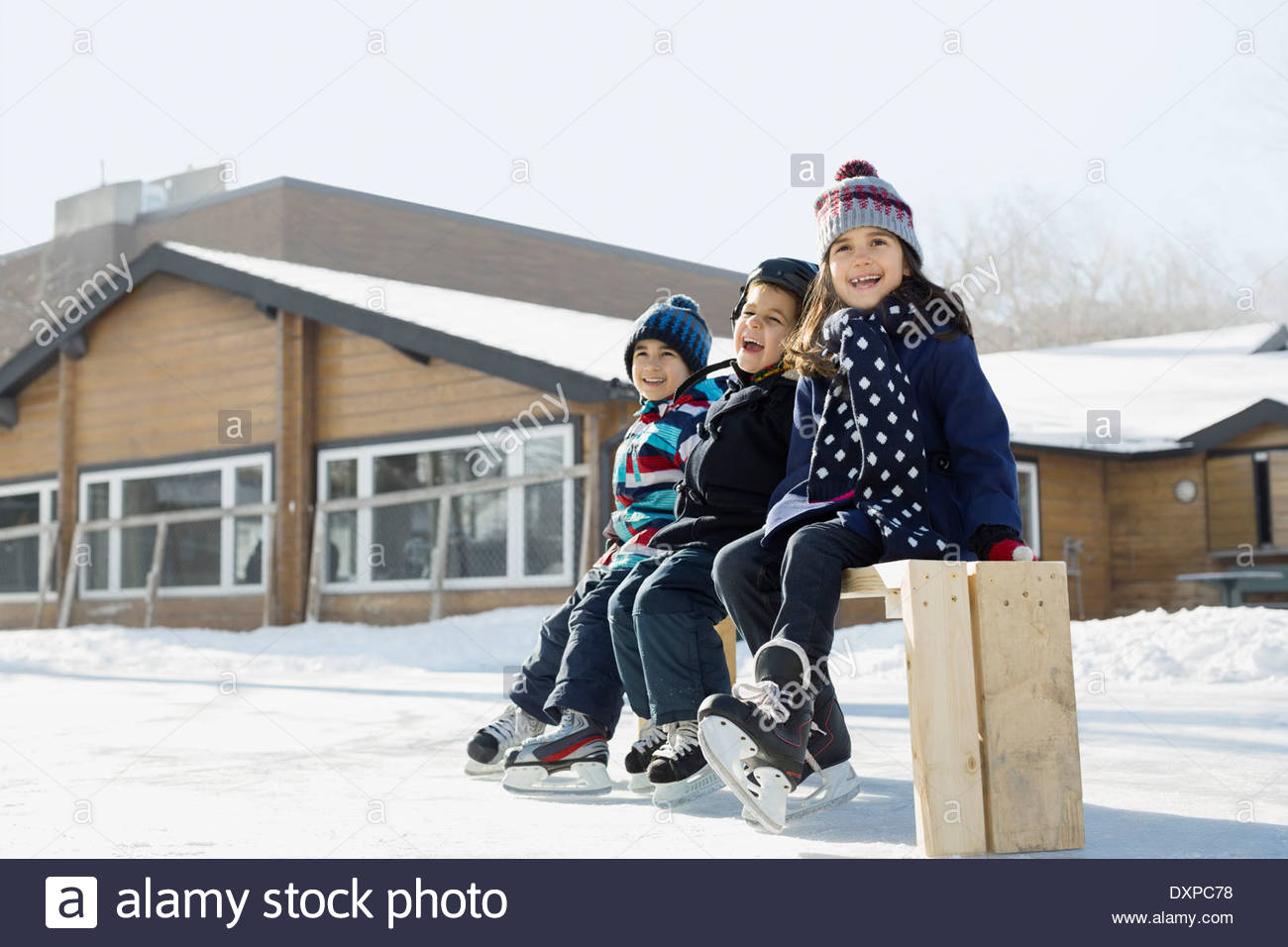 Siblings sitting on skating rink bench - Stock Image