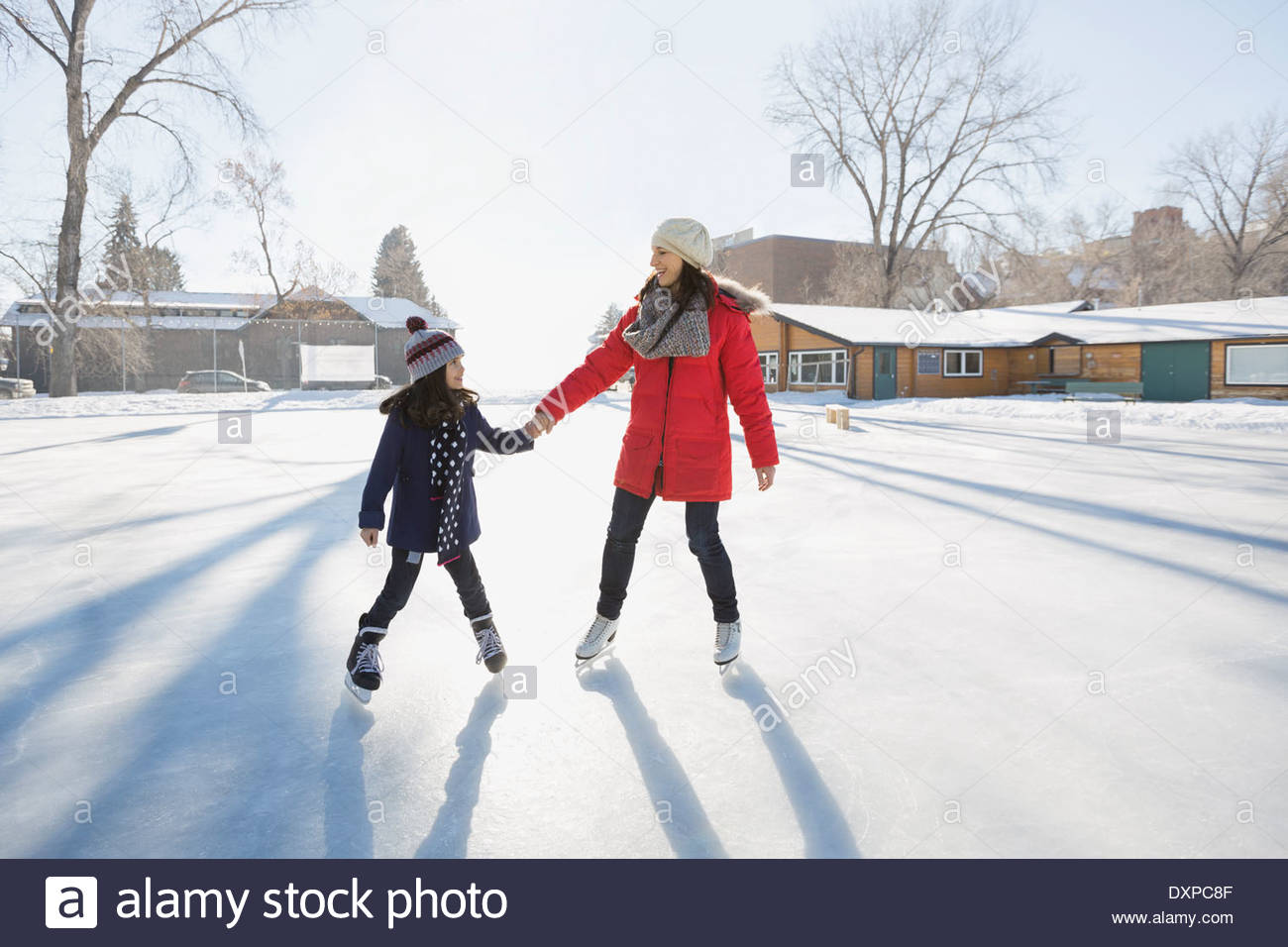 Mother and daughter ice-skating on rink - Stock Image