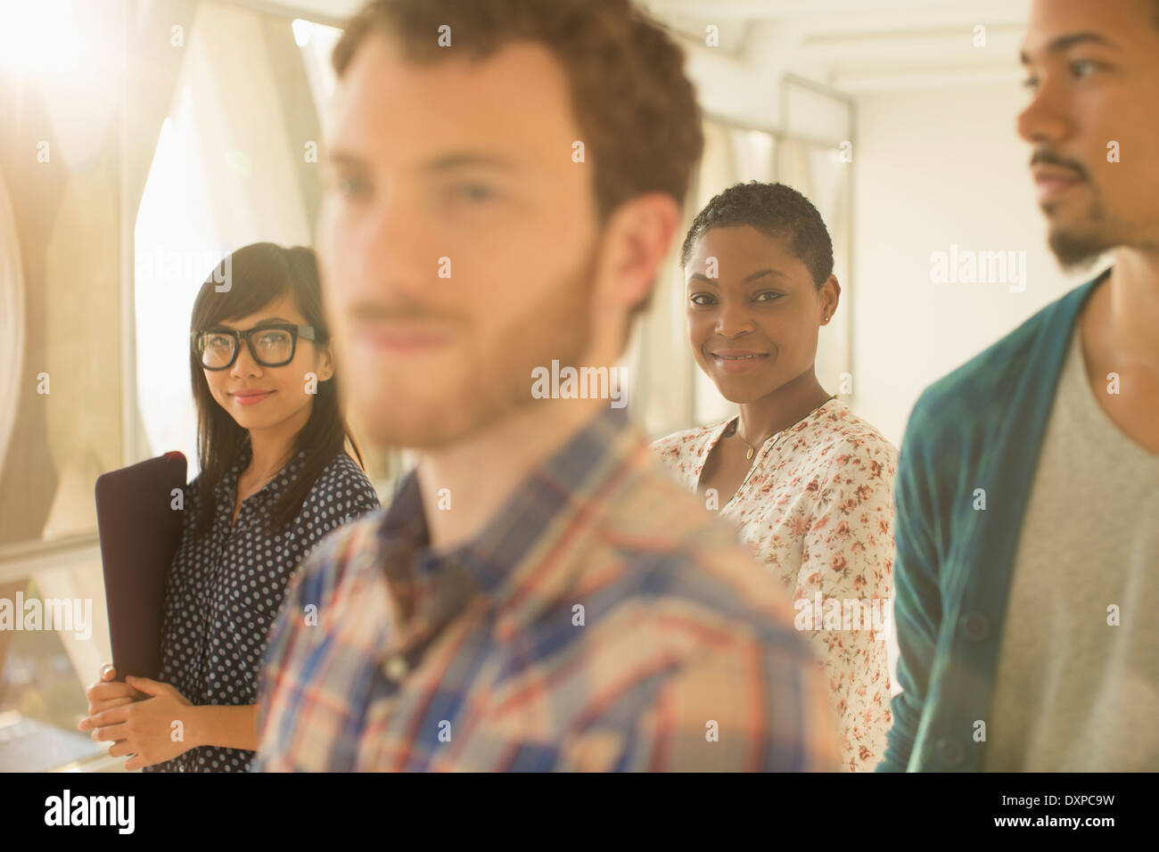 Portrait of smiling casual businesswoman with co-workers - Stock Image