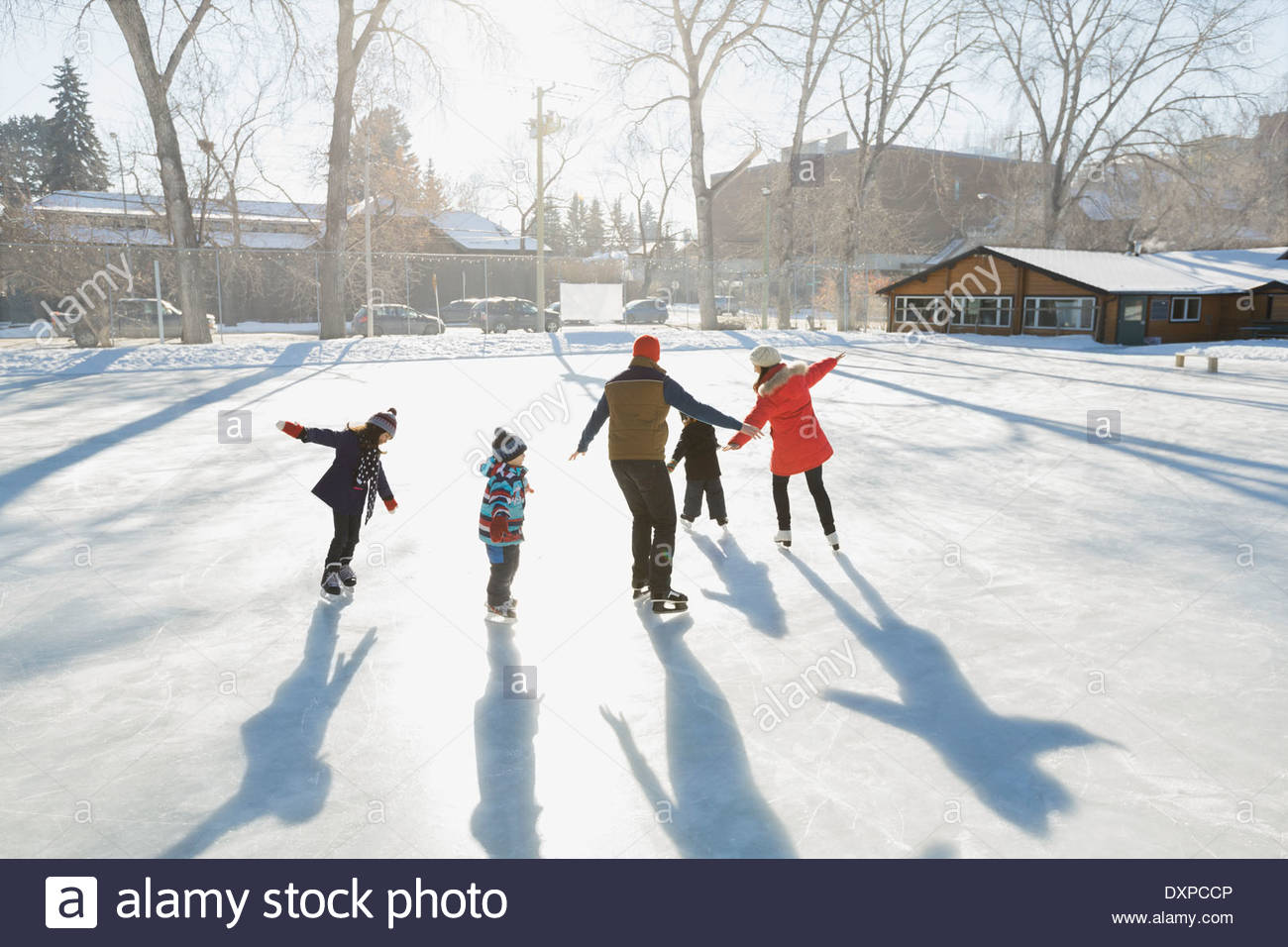 Family ice-skating on outdoor rink together - Stock Image