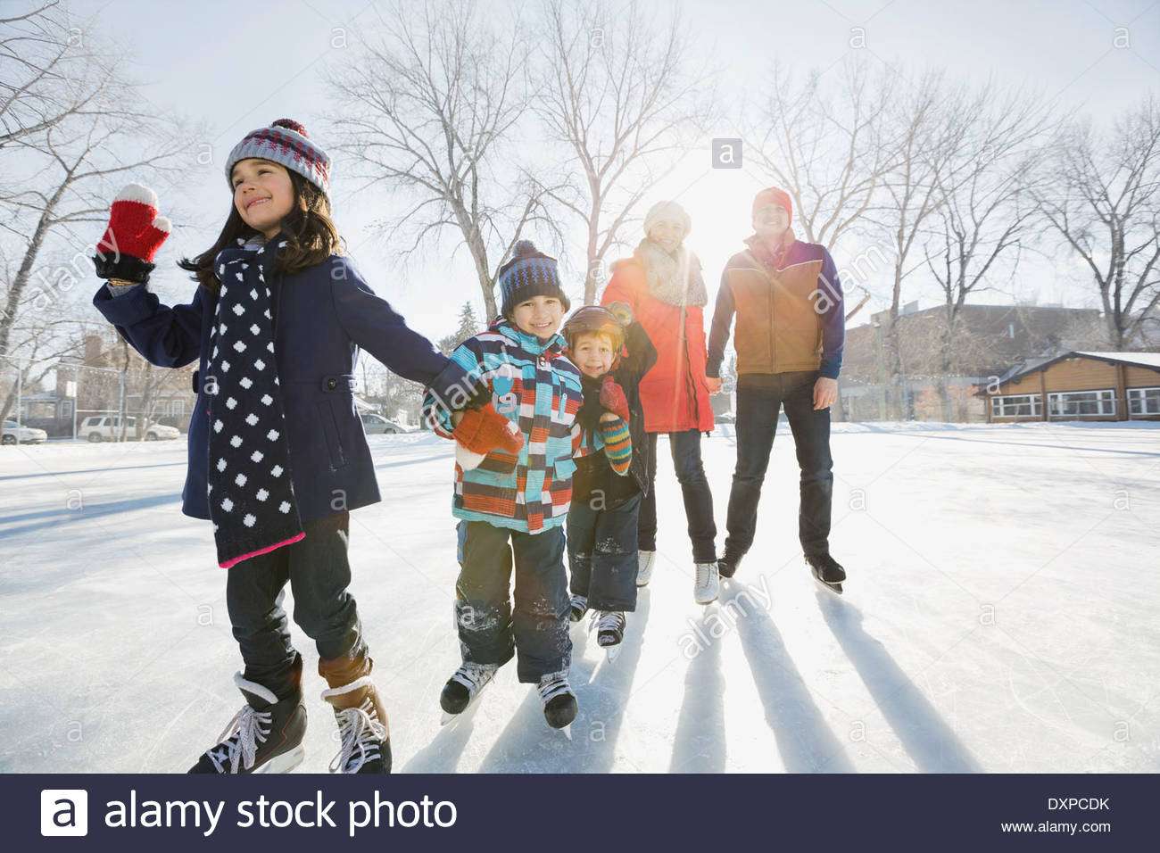 Family ice-skating on rink - Stock Image