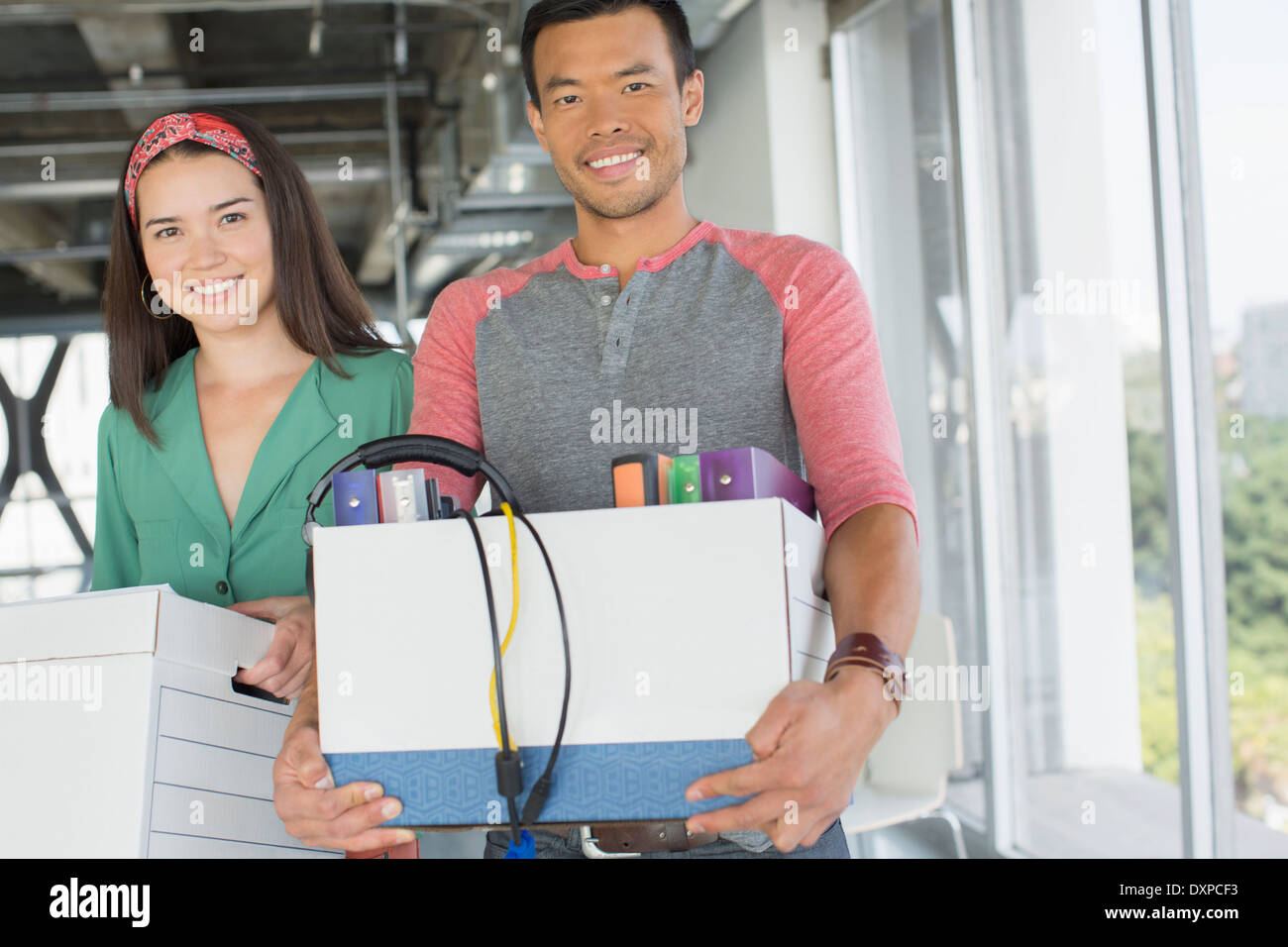 Portrait of happy casual business people carrying boxes of belongings in office - Stock Image