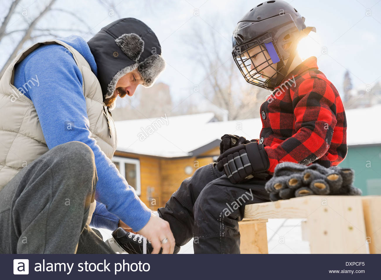 Father tying ice-skates for son - Stock Image