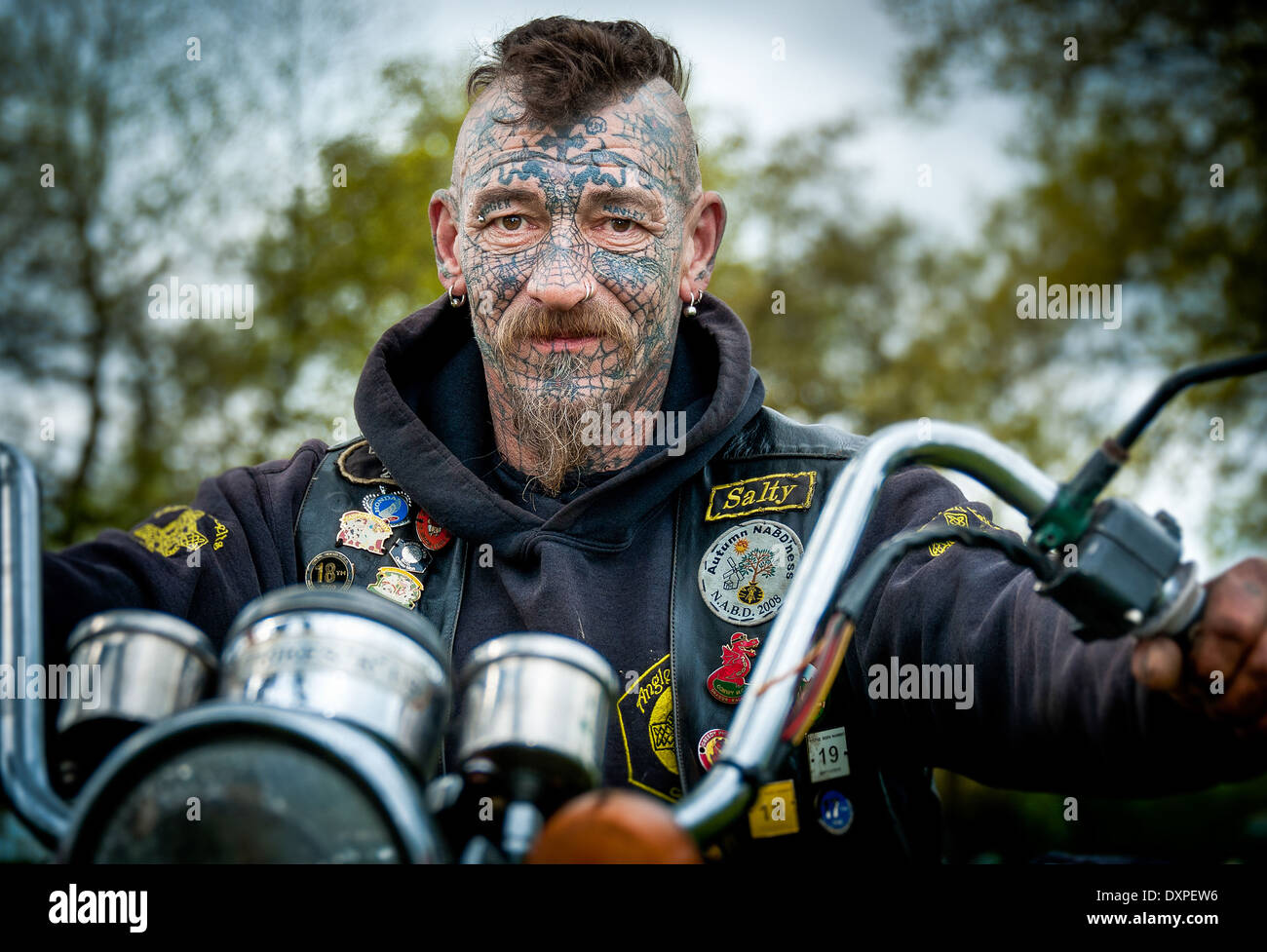 Male biker with facial tattoos and piercings - Stock Image