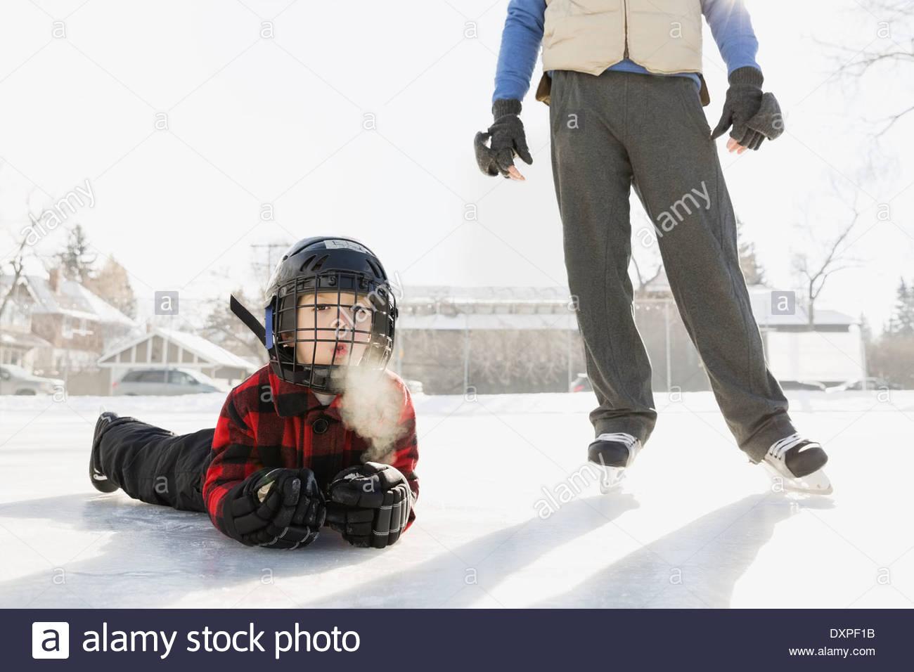 Boy lying on ice hockey rink - Stock Image