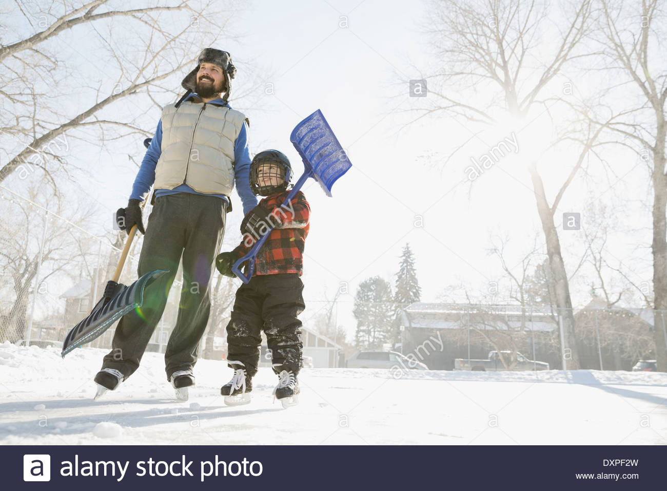 Father and son holding snow shovels on ice rink - Stock Image