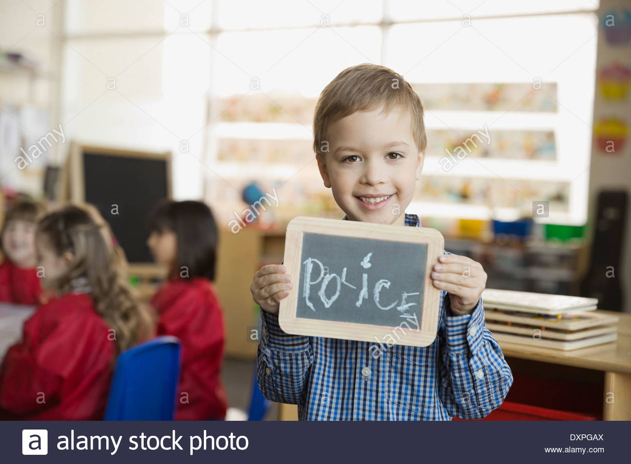 Elementary boy holding slate with 'Police' written on it - Stock Image