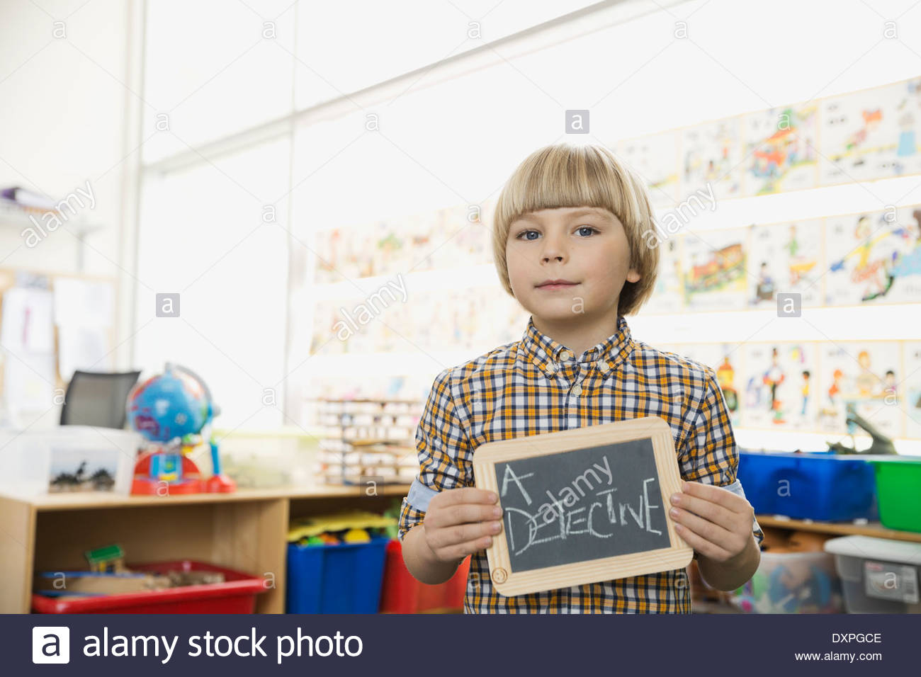 Confident boy holding slate with 'A Detective' written on it - Stock Image