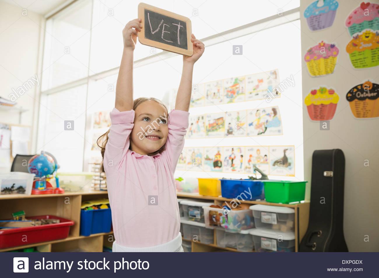 Smiling girl holding slate with 'Vet' written on it - Stock Image