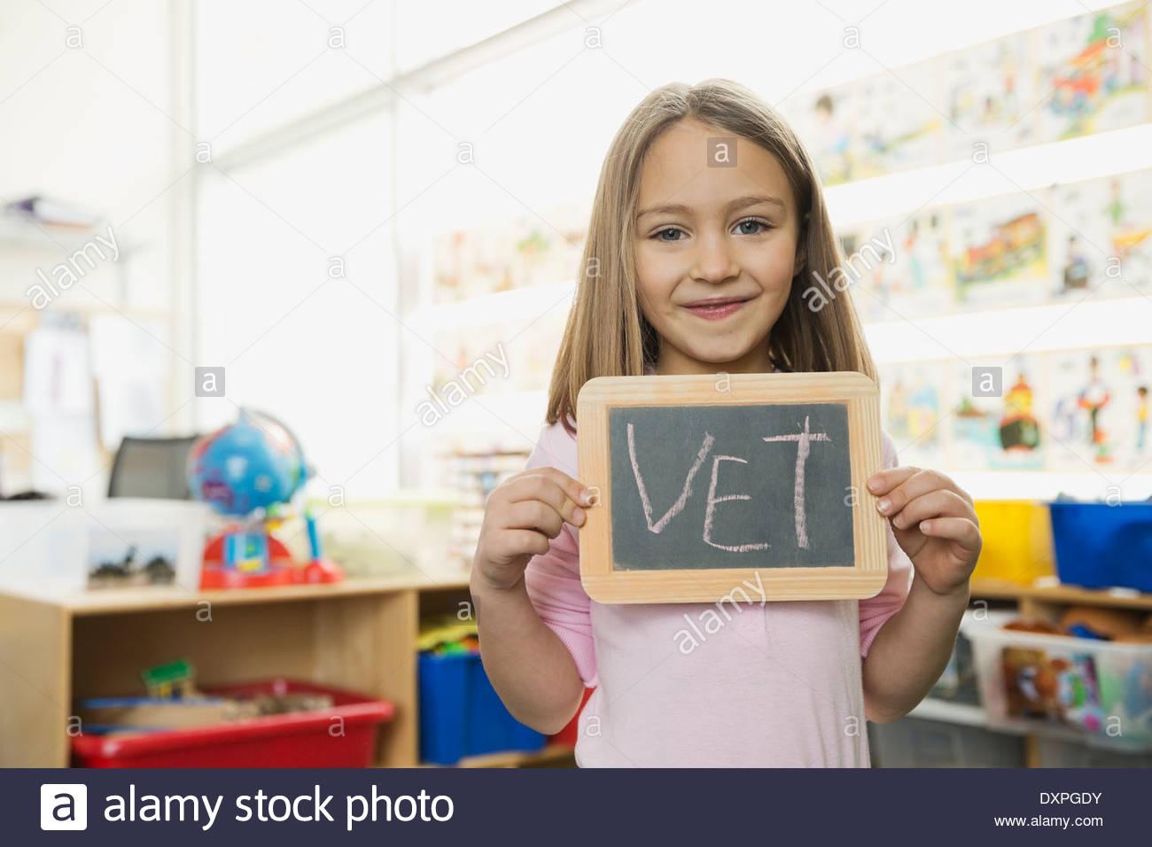 Portrait of girl holding slate with 'Vet' written on it - Stock Image