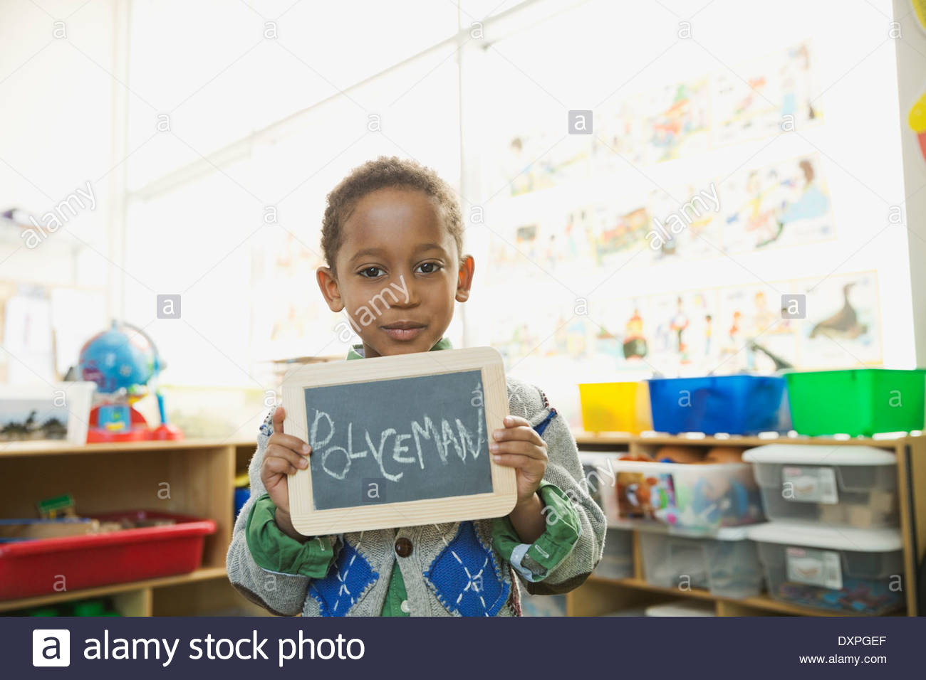 Portrait of boy holding slate with 'Policeman' written on it - Stock Image