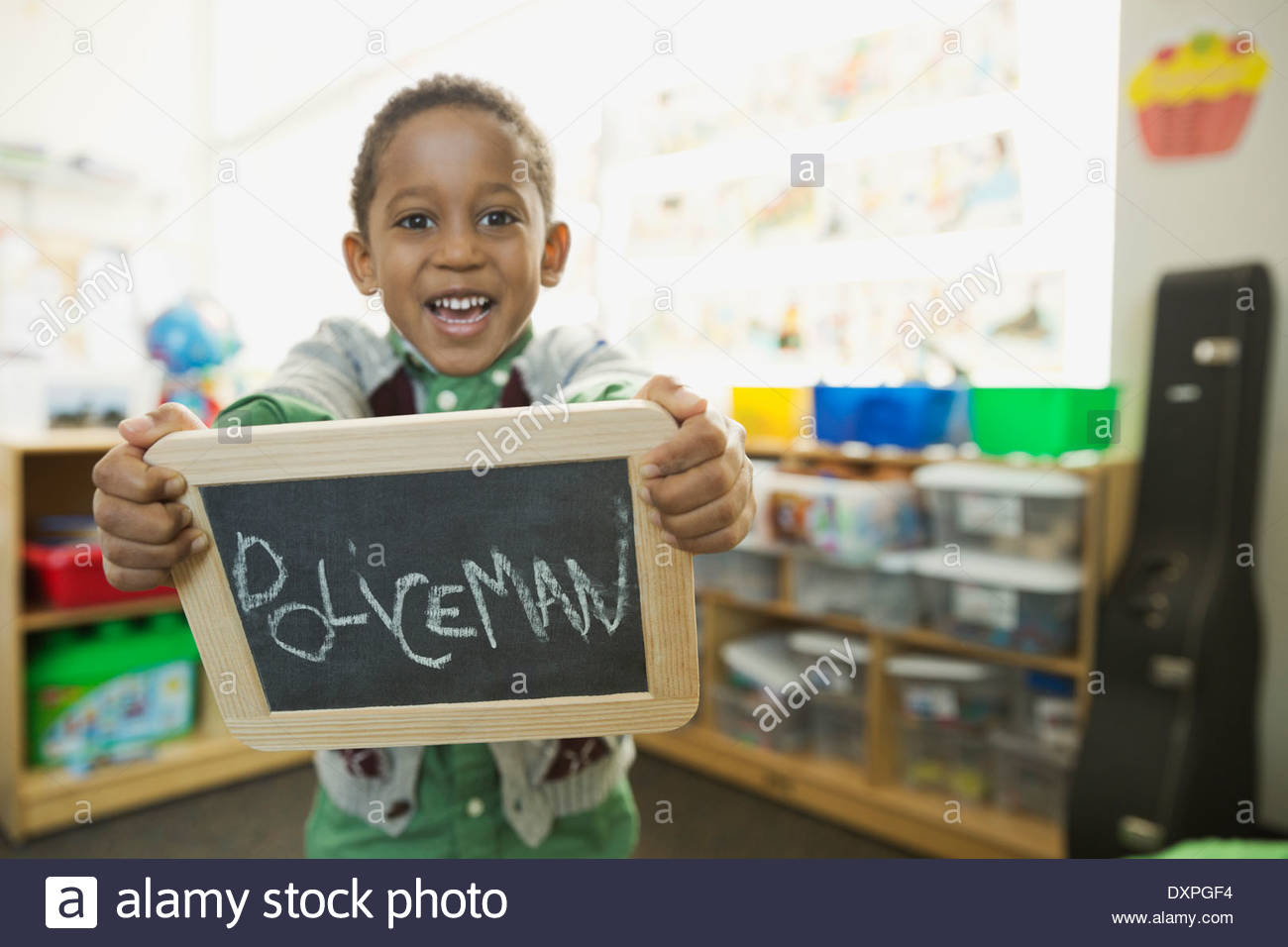 Boy holding slate with 'Policeman' written on it - Stock Image