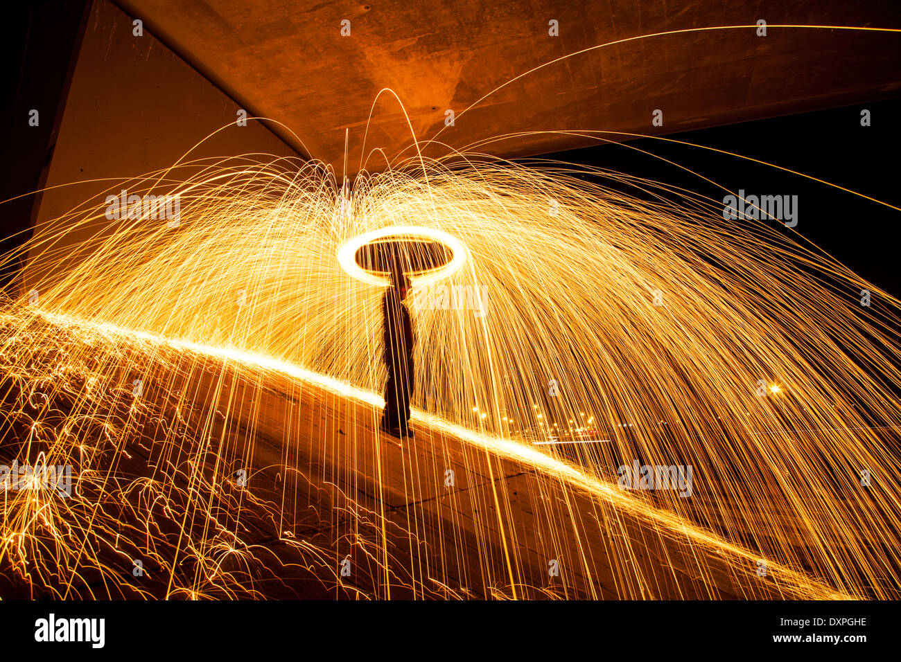 Sparks shower the ground as they fly away from a man spinning burning steel wool. - Stock Image