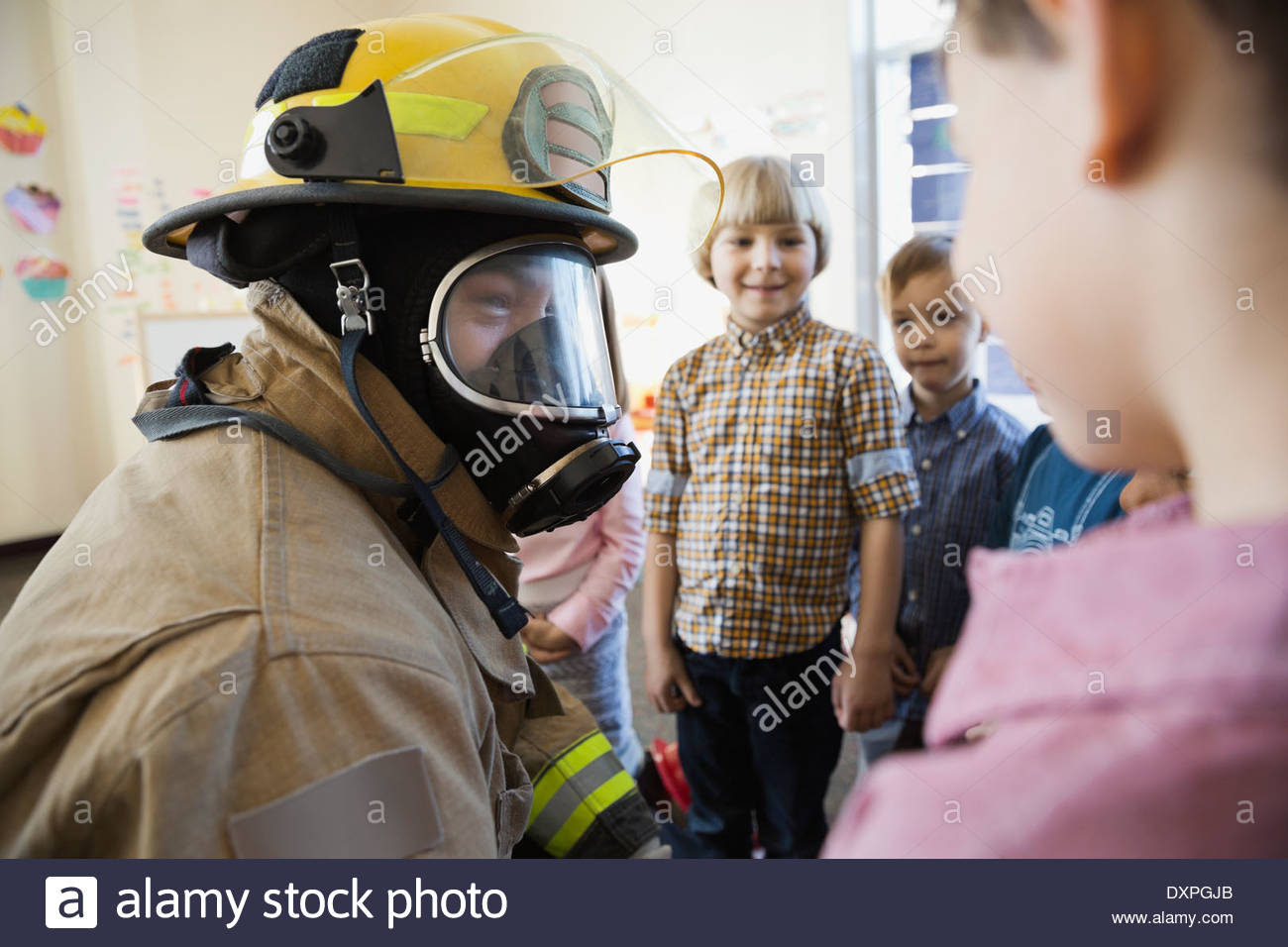 Firefighter giving presentation to elemetary children - Stock Image