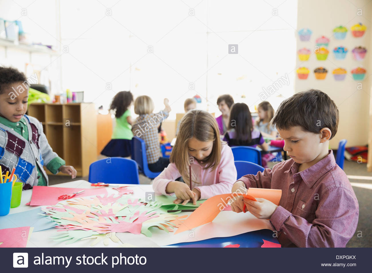 Elementary students tracing hands in class - Stock Image