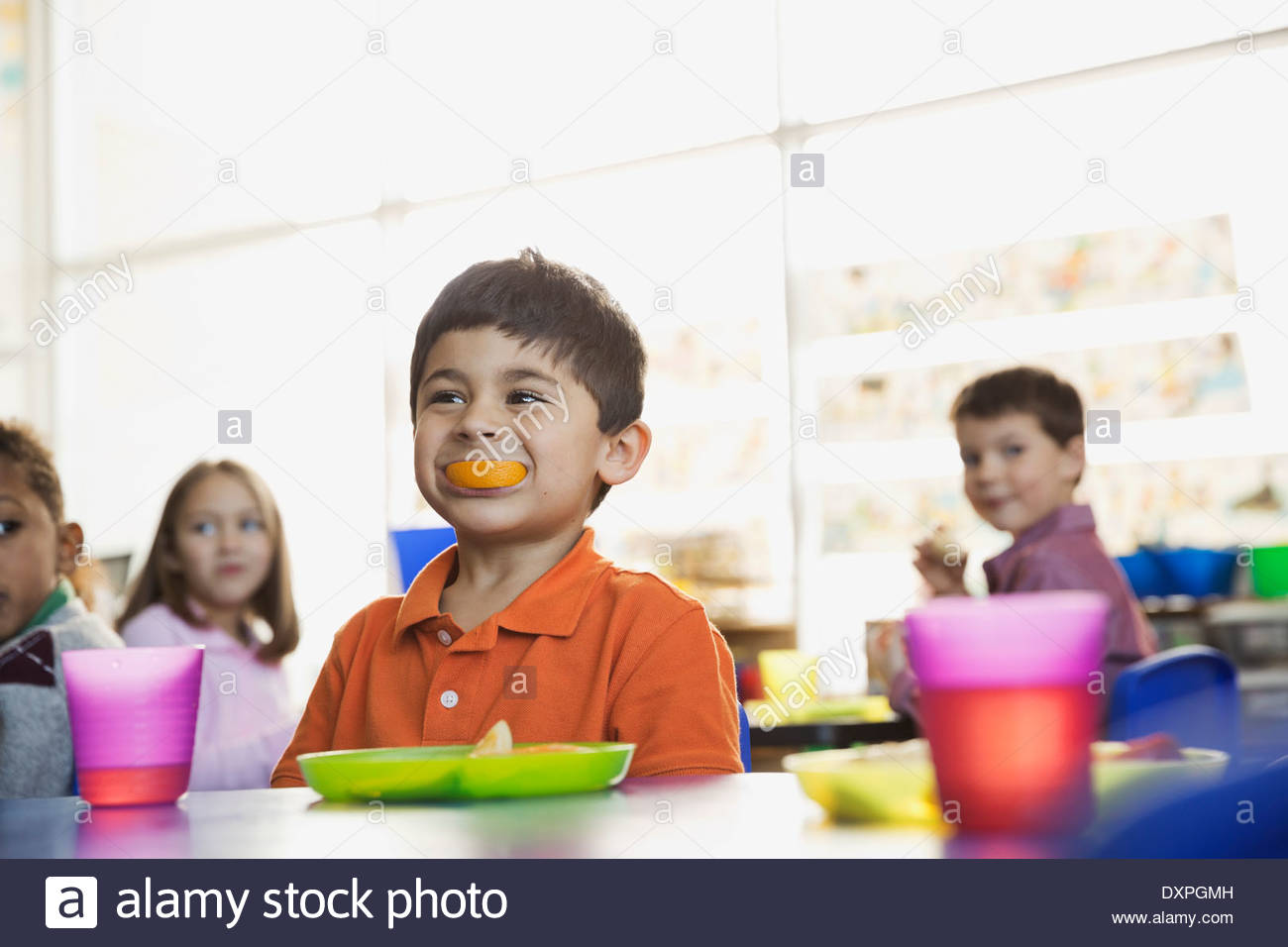 Playful boy holding orange slice in mouth at school at snack time - Stock Image