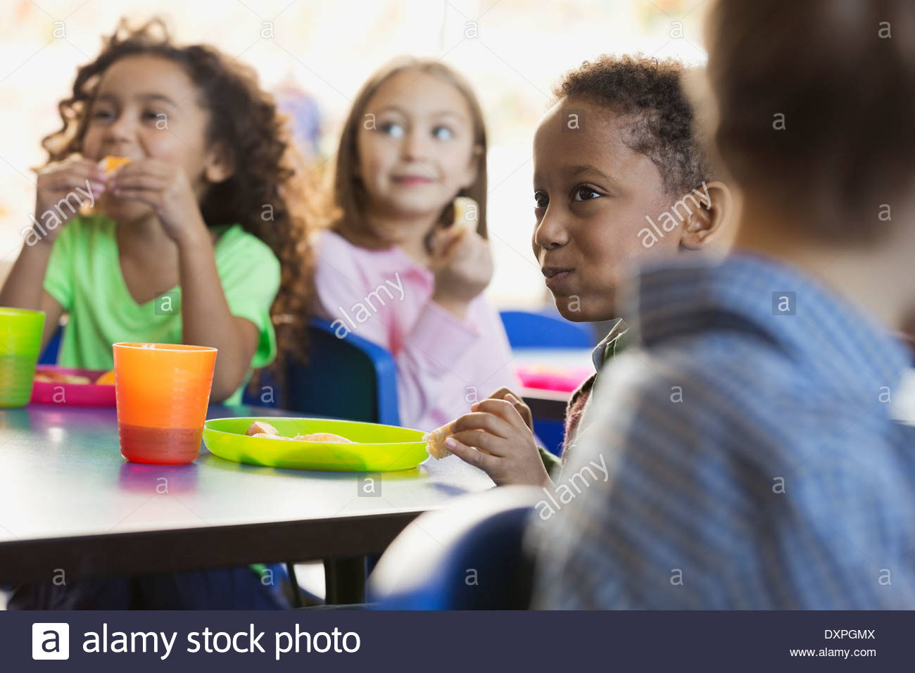 Children eating snacks in elementary school classroom - Stock Image