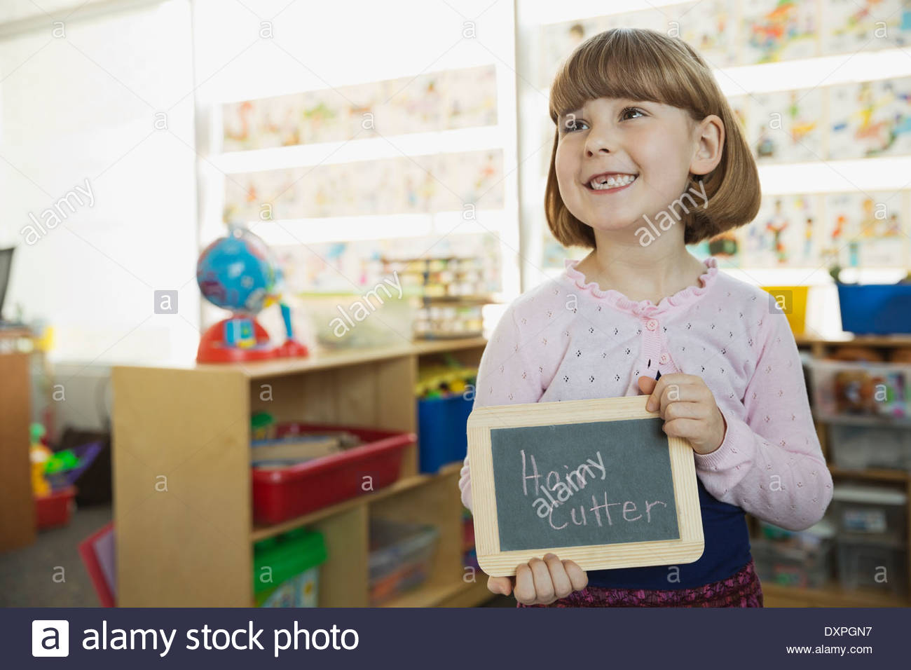 Cute girl holding slate with 'Hair Cutter' written on it - Stock Image