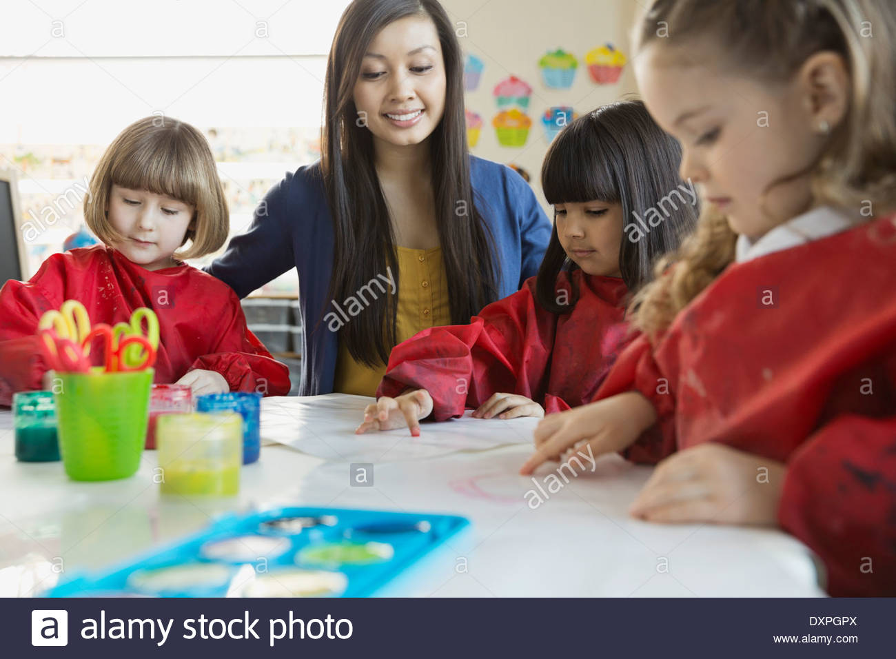 Teacher with students in art class - Stock Image