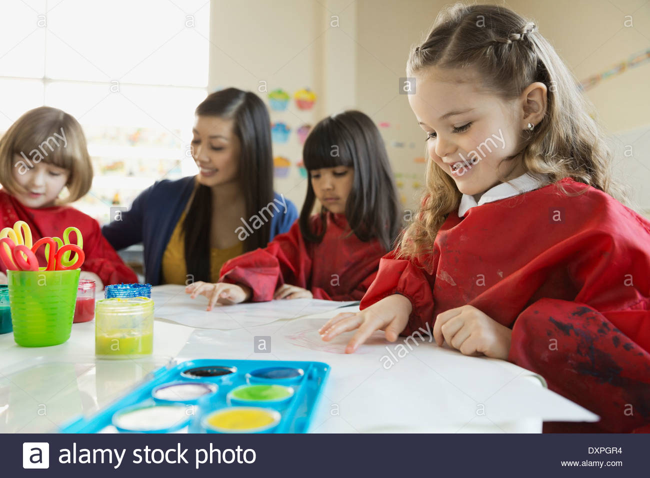 Teacher with girls finger painting in art class - Stock Image
