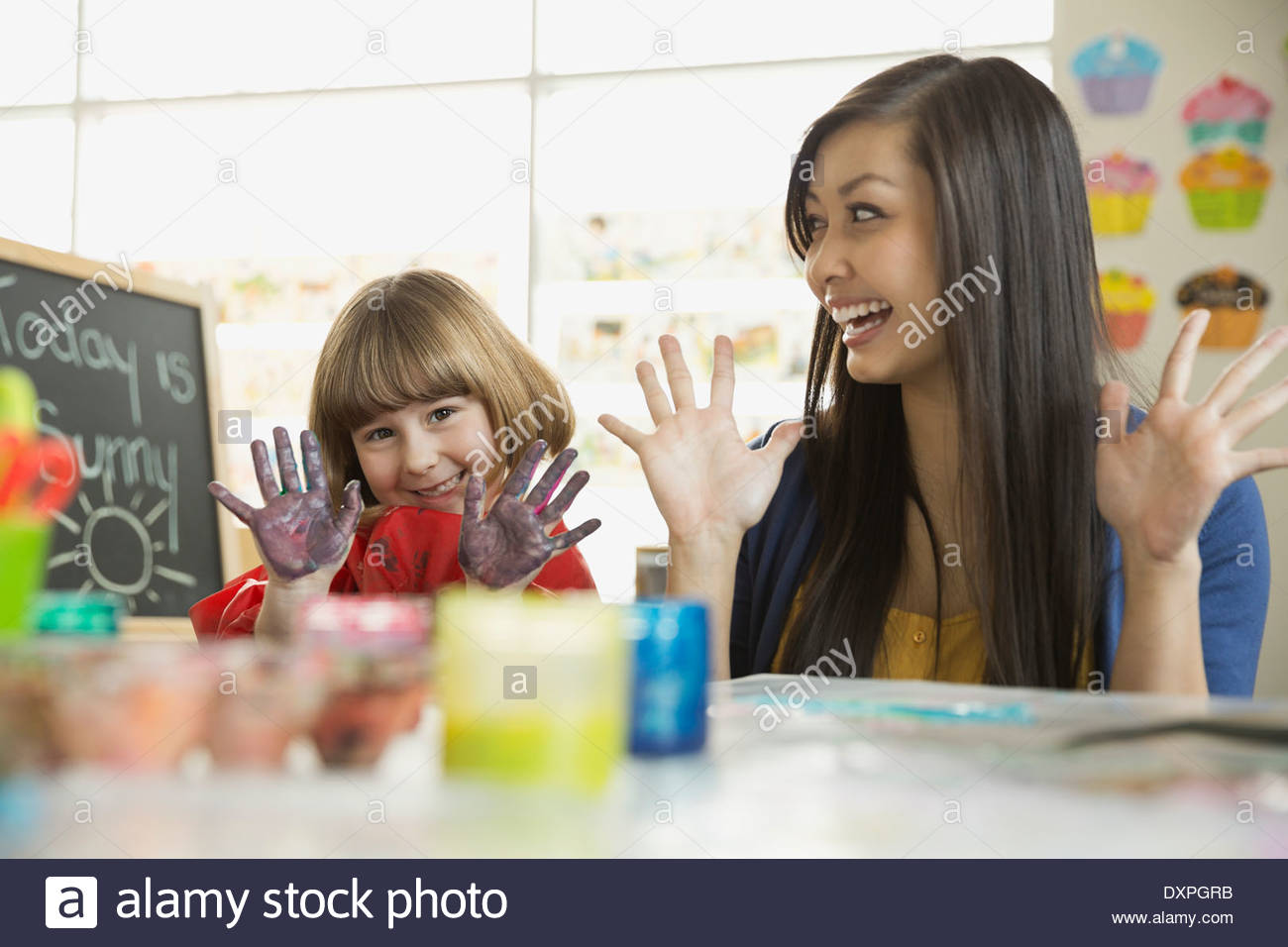 Teacher with girl finger painting in art class - Stock Image