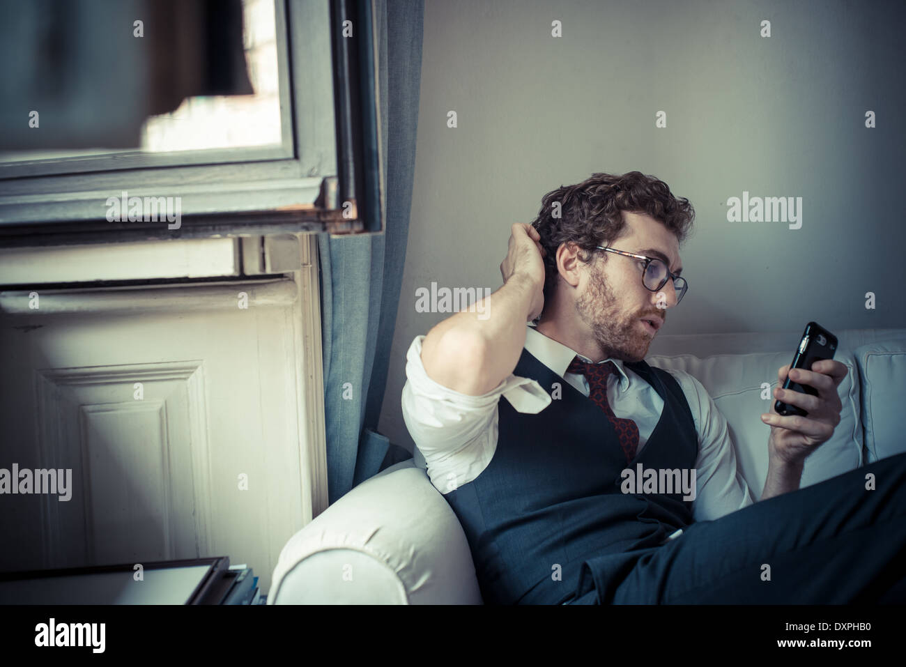 elegant attractive fashion hipster man on the phone at home - Stock Image