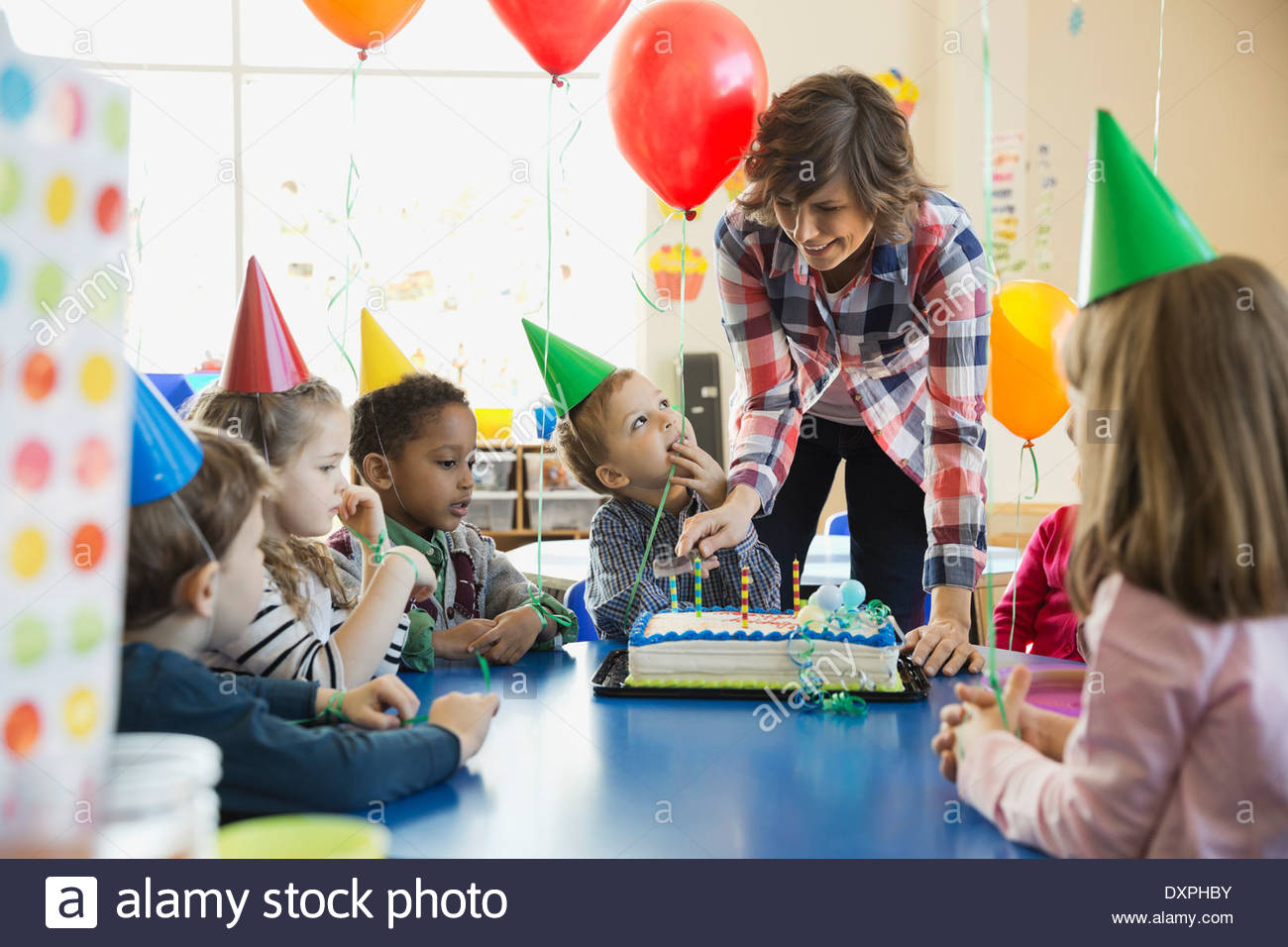 Teacher and kids celebrating birthday in school - Stock Image