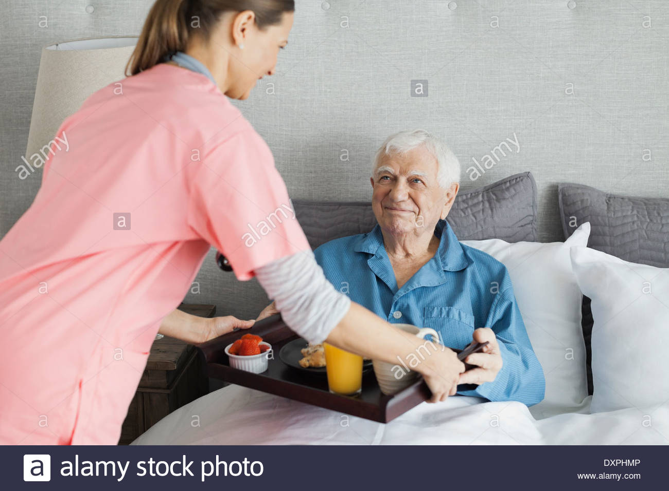 Home care nurse serving breakfast to senior man - Stock Image