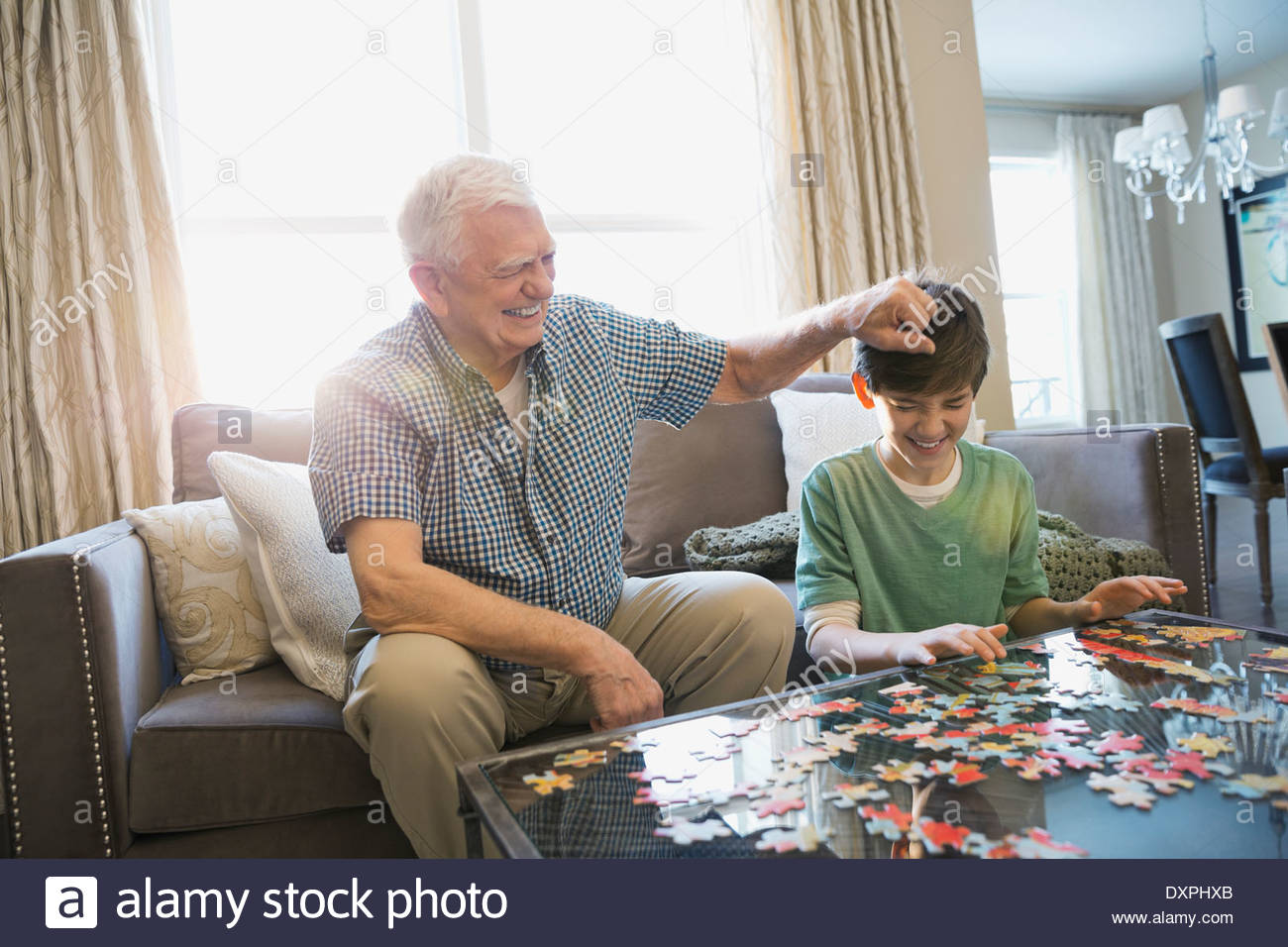 Playful grandfather and grandson solving puzzle at home - Stock Image