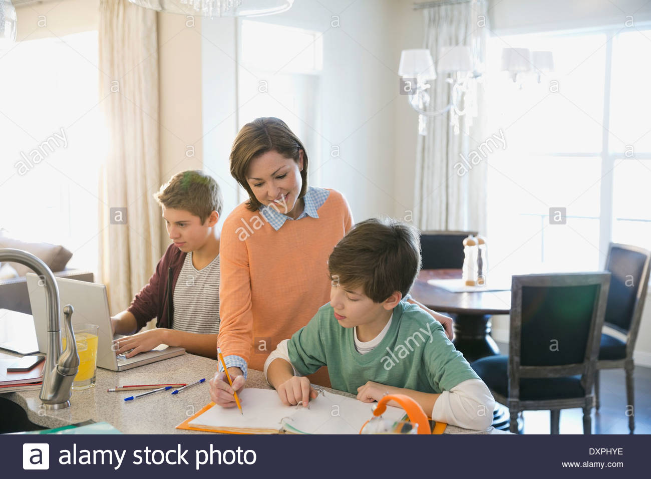 Woman assisting son with homework - Stock Image