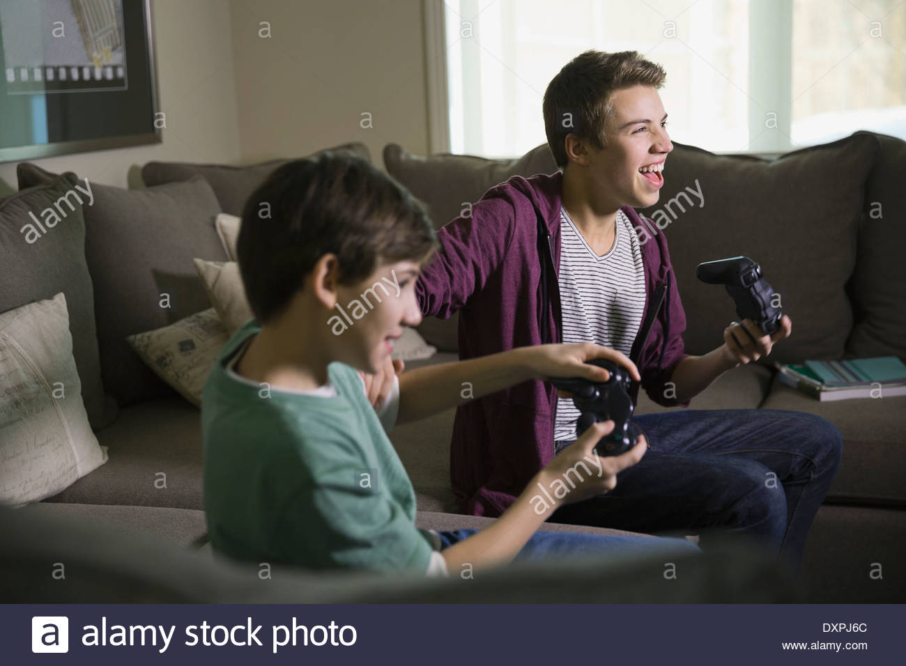 Excited brothers playing video games on sofa - Stock Image