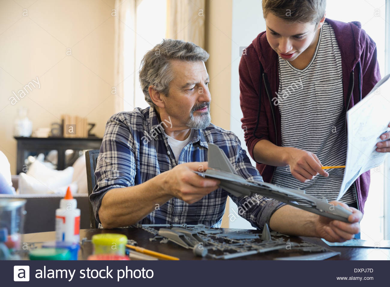 Grandson and grandfather building airplane model at home - Stock Image