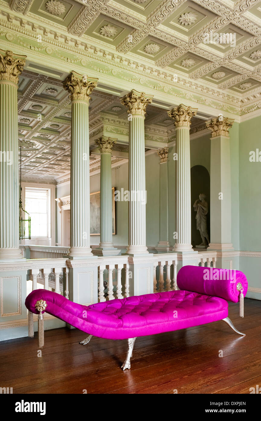 A pink buttoned Jaba Couch by Brazier-Jones on a classical style landing with coffered ceiling panels and acanthus leaf columns - Stock Image