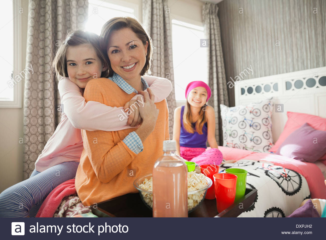 Portrait of daughter embracing mother at slumber party - Stock Image