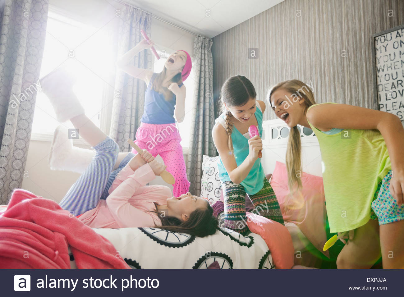Cheerful girls singing into hairbrushes at slumber party - Stock Image