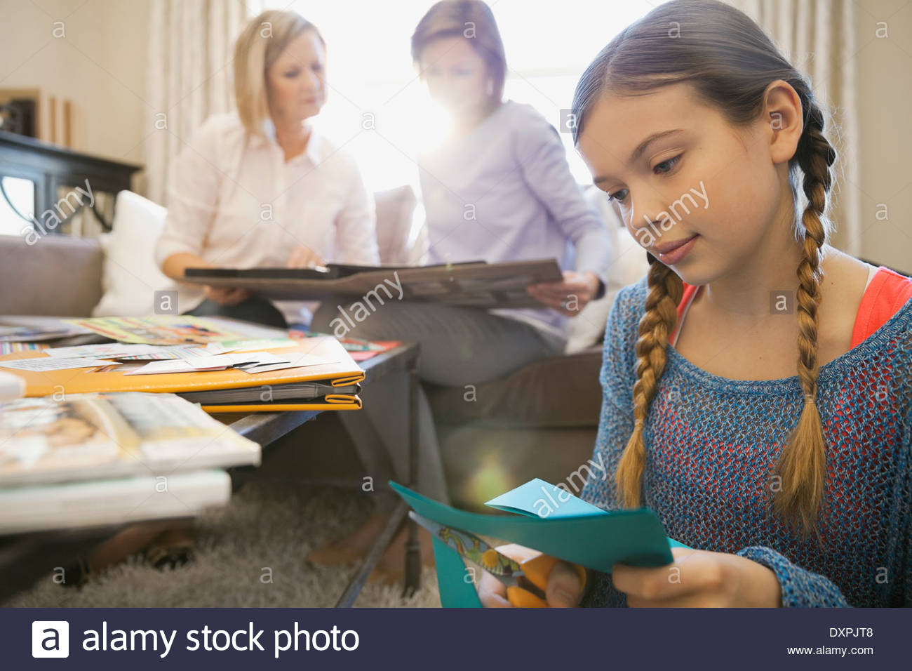 Girl scrapbooking at home - Stock Image