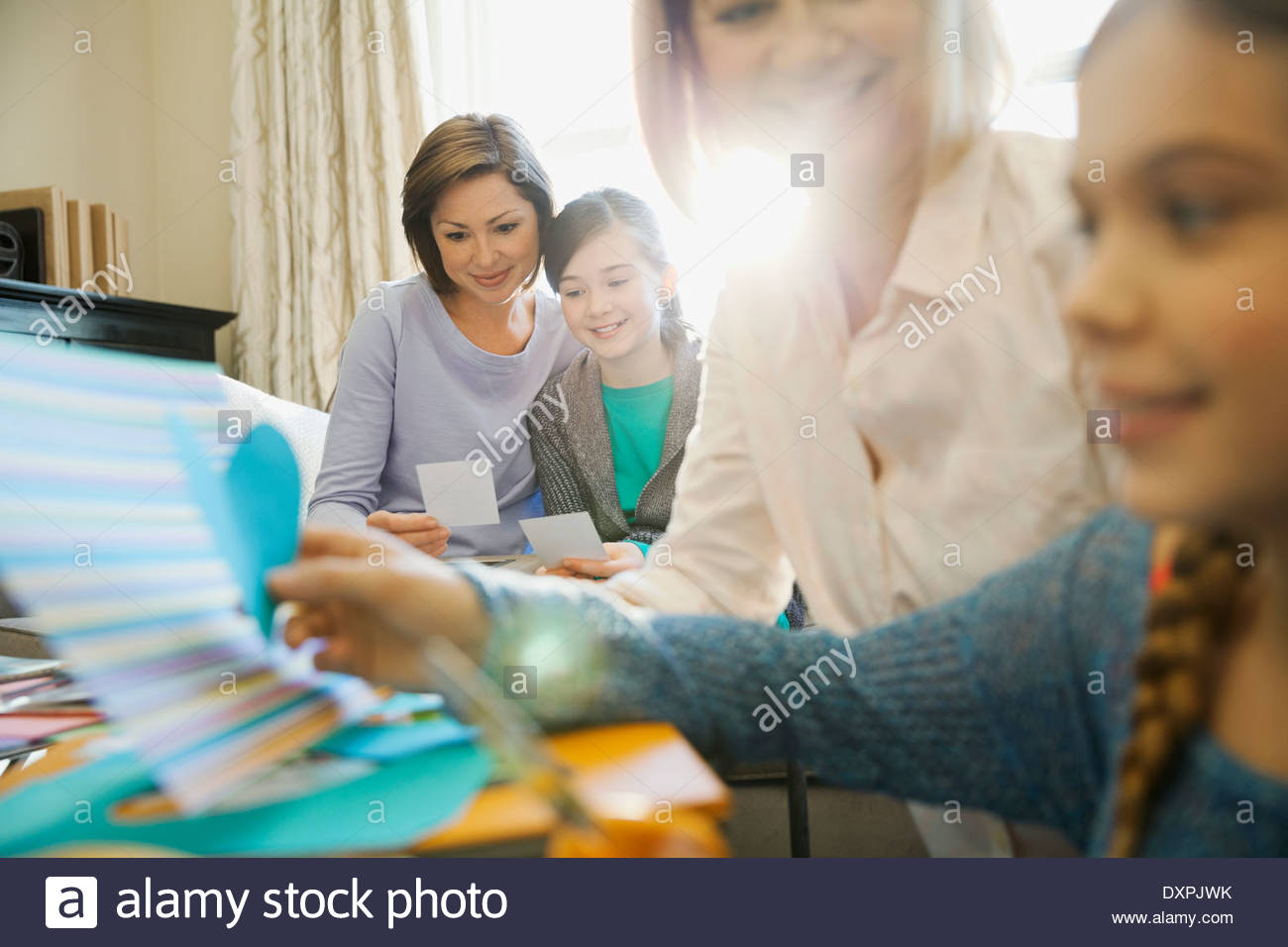 Smiling mother and daughter looking at photos while scrapbooking - Stock Image
