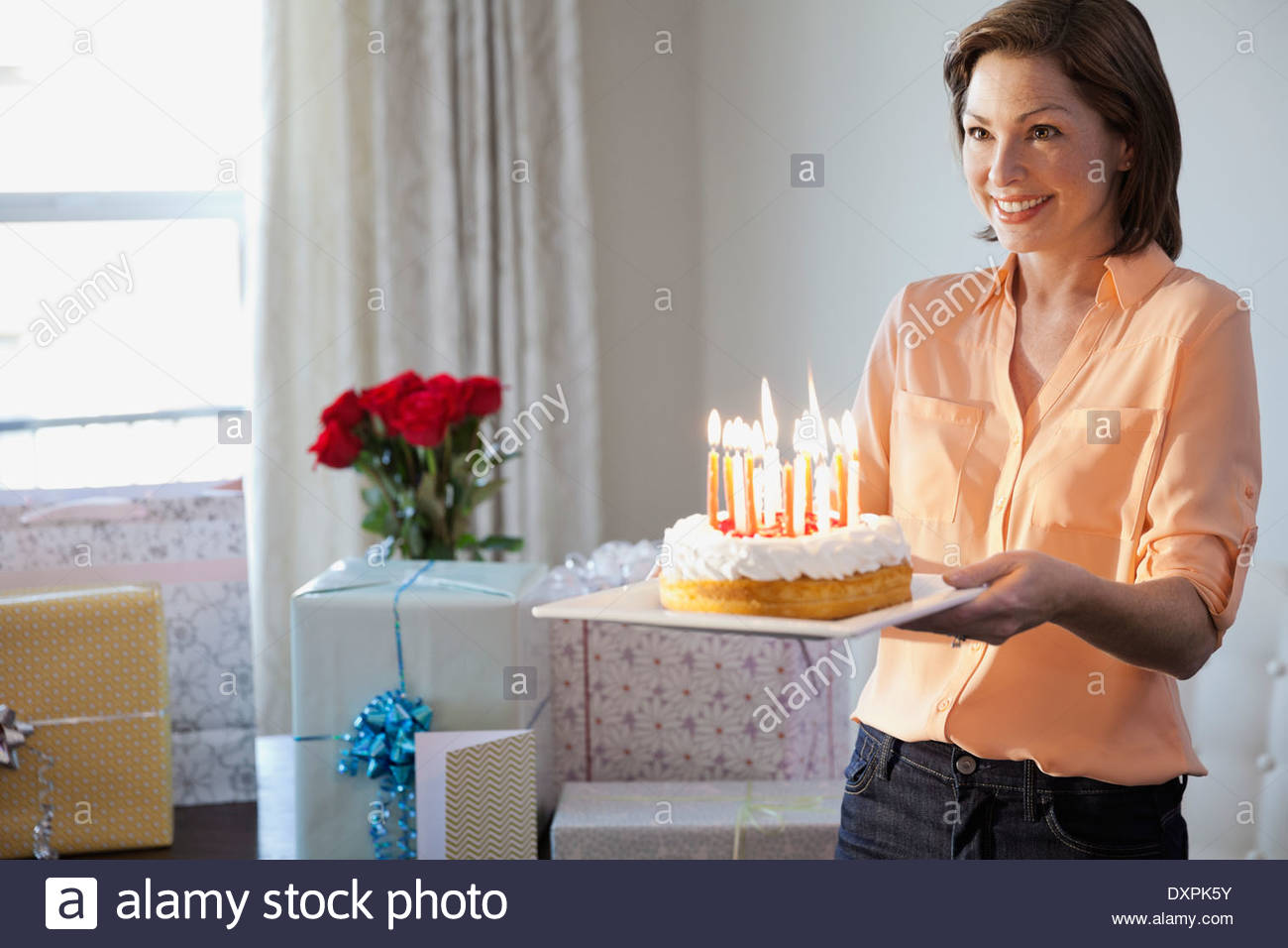Smiling woman holding birthday cake at home - Stock Image
