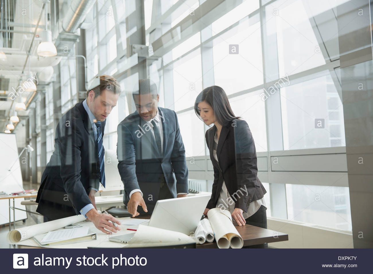 Business people reviewing blueprints at desk - Stock Image