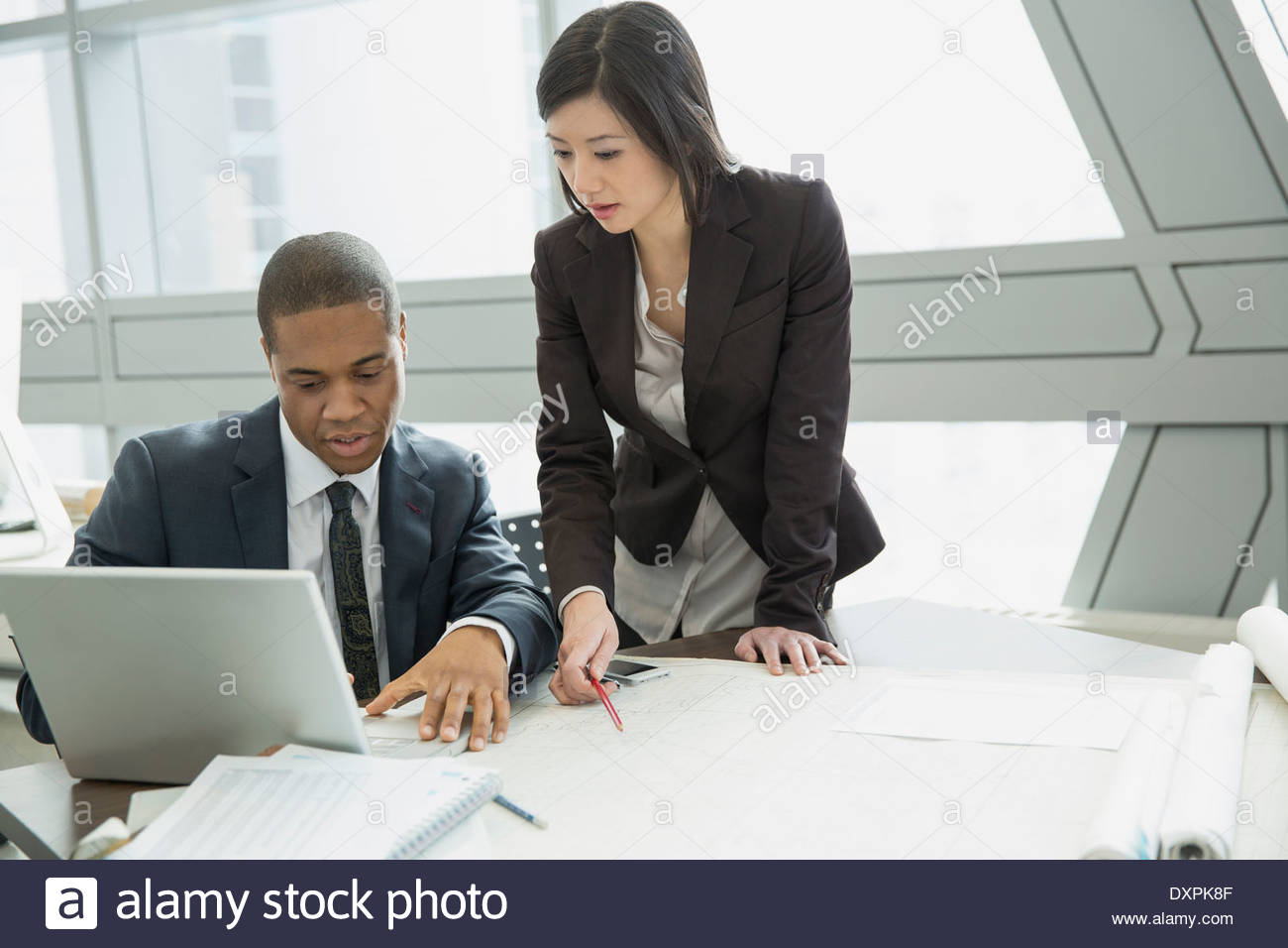Colleagues using laptop and reviewing blueprints at desk - Stock Image