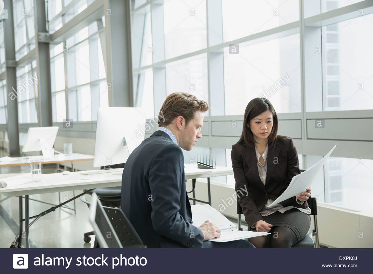 Business people reviewing paperwork in office - Stock Image