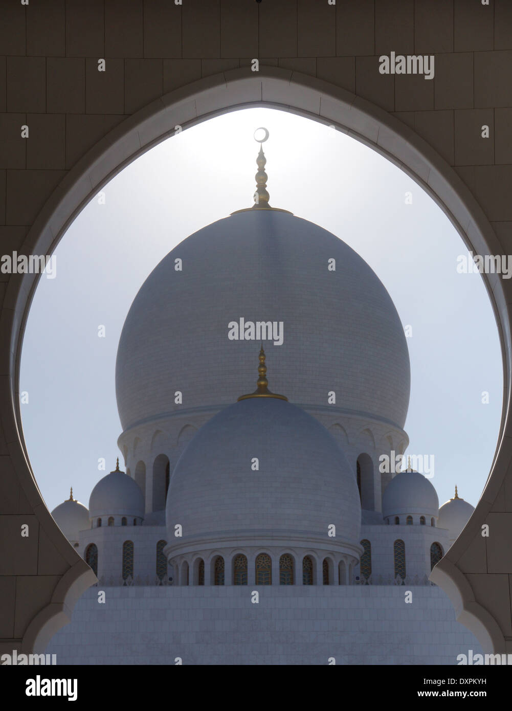 Looking through a dome shaped wall to the main dome with its surrounding domes at sunset at the Sheikh Zayed Grand Mosque - Stock Image